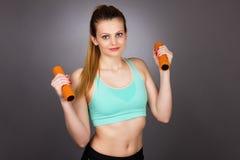 Femme heureuse de forme physique avec l'élaboration d'haltères Photographie stock libre de droits