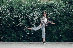 Femme heureuse de hippie dans des lunettes de soleil ayant l'amusement sur le fond du bl Image stock