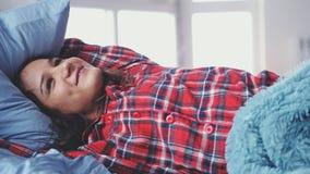 Femme heureuse de jeune brune somnolente se situant dans le lit se réveillant et souriant Photo libre de droits