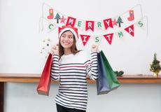 Femme heureuse de l'Asie de sourire tenant beaucoup le panier en partie, achat ch images libres de droits