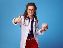 Femme heureuse de médecin avec la tirelire montrant des pouces sur le bleu images libres de droits