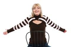 Femme heureuse de Moyen Âge s'asseyant sur la présidence Photo libre de droits