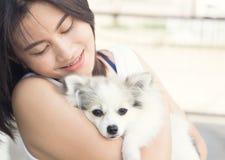 Femme heureuse de plan rapproché avec le chien pomeranian blanc en main, healt d'animal familier Photographie stock libre de droits