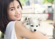 Femme heureuse de plan rapproché avec le chien pomeranian blanc en main, healt d'animal familier Photographie stock