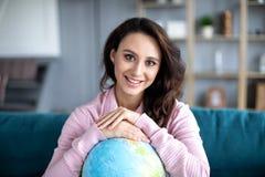 Femme heureuse de portrait prévoyant des vacances de voyage ou d'été avec le globe du sourire du monde photo stock