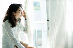 Femme heureuse de portrait regardant de la fenêtre photos libres de droits