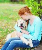 Femme heureuse de propriétaire étreignant le chien de golden retriever Images libres de droits