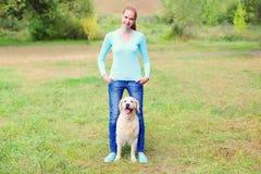 Femme heureuse de propriétaire avec le chien de golden retriever marchant ensemble Photos libres de droits