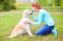 Femme heureuse de propriétaire embrassant le chien de golden retriever Photographie stock libre de droits