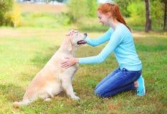 Femme heureuse de propriétaire frottant le chien de golden retriever sur l'herbe Image libre de droits
