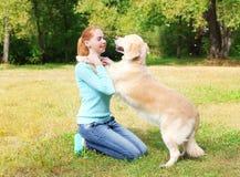 Femme heureuse de propriétaire jouant avec le chien de golden retriever Photographie stock