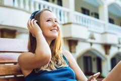 Femme heureuse de smartphone détendant près de l'esprit de écoute de piscine Image stock
