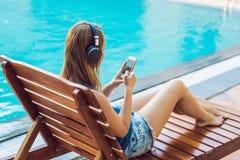 Femme heureuse de smartphone détendant près de la piscine écoutant avec des earbuds couler la musique Belle fille l'employant Images stock
