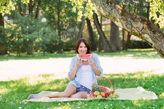 Femme heureuse de sourire mangeant une pastèque en parc Photographie stock libre de droits