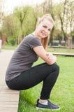 Femme heureuse de sourire s'asseyant et détendant dehors en nature photo stock