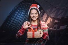 Femme heureuse de sourire touchant un ruban rouge sur un présent Image libre de droits