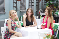 Femme heureuse de trois amies s'asseyant à une table pendant l'été c Photos libres de droits