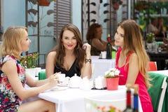 Femme heureuse de trois amies s'asseyant à une table pendant l'été c Image libre de droits