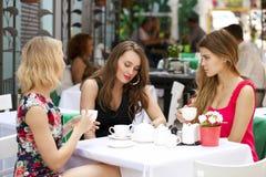 Femme heureuse de trois amies s'asseyant à une table pendant l'été c Image stock
