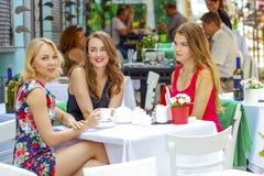 Femme heureuse de trois amies s'asseyant à une table pendant l'été c Images libres de droits