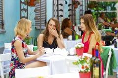 Femme heureuse de trois amies s'asseyant à une table pendant l'été c Photo libre de droits