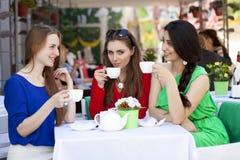 Femme heureuse de trois amies s'asseyant à une table pendant l'été c Photographie stock