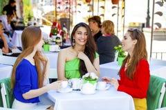 Femme heureuse de trois amies s'asseyant à une table pendant l'été c Photographie stock libre de droits