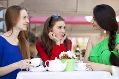 Femme heureuse de trois amies s'asseyant à une table pendant l'été c Images stock