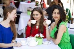Femme heureuse de trois amies s'asseyant à une table pendant l'été c Photos stock