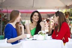 Femme heureuse de trois amies s'asseyant à une table pendant l'été c Photo stock
