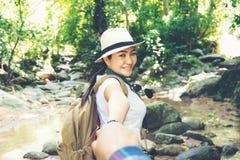 Femme heureuse de voyageur tenant la main de son ami tout en marchant dans la chute de l'eau Image libre de droits
