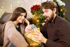 Femme heureuse donnant le cadeau de Noël à l'ami étonné Photos stock