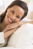 Femme heureuse détendant sur le coussin à la maison Image libre de droits
