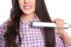 Femme heureuse employant le fer de cheveux sur le fond blanc image libre de droits