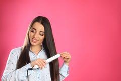 Femme heureuse employant le fer de cheveux sur le fond de couleur photographie stock