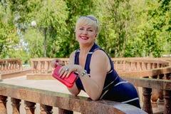 Femme heureuse en parc avec un sac à main rouge Images libres de droits