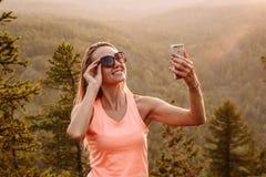 Femme heureuse en protection solaire photographiée dans les montagnes en été Les rayons du coucher du soleil dans la photo Selfie photographie stock