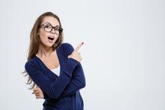 Femme heureuse en verres dirigeant le doigt loin images stock