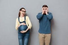 Femme heureuse enceinte se tenant près de l'homme criard Image libre de droits
