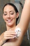 Femme heureuse enlevant des cheveux d'aisselle dans la douche Image stock