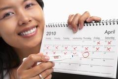 Femme heureuse, essai de grossesse positif et calendrier Image libre de droits