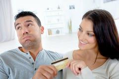 Femme heureuse et ami frustrant donnant la carte de cedit à Image libre de droits