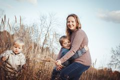 Femme heureuse et deux fils dans un domaine en automne photo libre de droits
