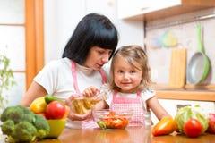 Femme heureuse et enfant préparant la nourriture saine ensemble Photos libres de droits