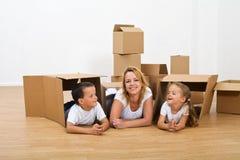 Femme heureuse et enfants détendant dans leur nouvelle maison Photographie stock libre de droits