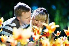 Femme heureuse et homme élégant parmi des fleurs Photographie stock