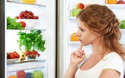 Femme heureuse et réfrigérateur ouvert avec des fruits, des légumes et lui Image libre de droits