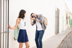Femme heureuse faisant cliquer sur des photos par un photographe dehors Photos libres de droits
