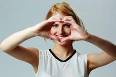 Femme heureuse faisant la forme de coeur avec des mains Photographie stock