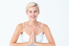 Femme heureuse faisant le yoga souriant à l'appareil-photo photos stock